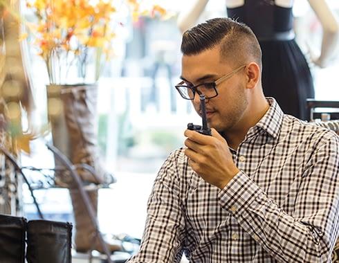 Retail sales clerk talking on a Motorola two way radio