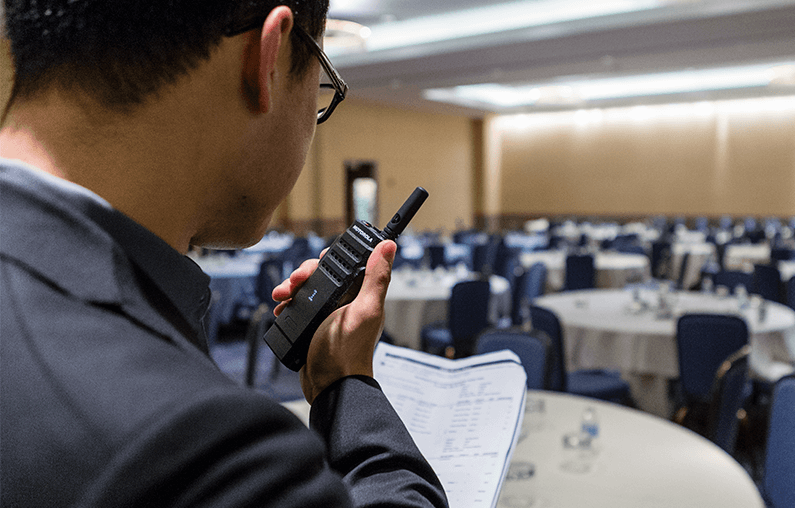 A hotel manager uses a SL300 Motorola Solutions two way radio.